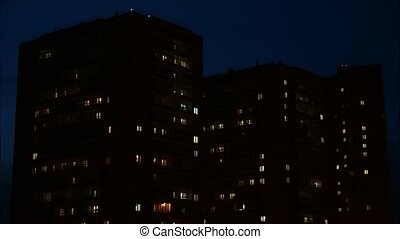 Close up view to windows in apartment buildings at night,