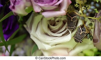 Close-up view to women's brooch of two owls on roses flowers...
