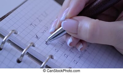 Motivation, management, productivity, success, planning, reminder, goals concept. Close up: woman hand putting mark on check boxes of to do list in personal vintage notebook organizer - slow motion