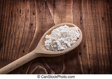 close up view wooden spoon with flour on vintage board