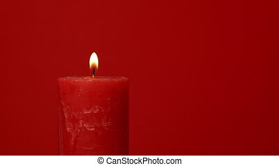 Close up vivid red candle trembling flame