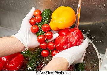 Close up washing vegetables under running tap water.