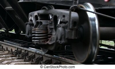 Close up wheels of iron ore cargo freight train passing. Slow motion