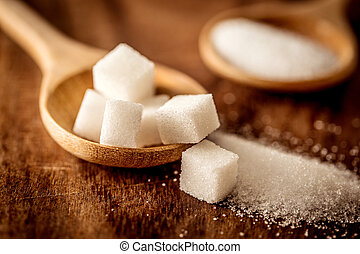 Close up white sugar cubes and cane in wooden spoon on the table