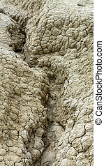 Close-up with dried ground covered with cracks. Natural dry soil texture, brown drought theme in rural arid area, background for design.