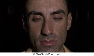 Close up with face of tired man opening his eyes