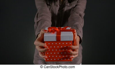 Close up with hands of a woman offering birthday present