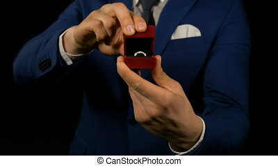 Close up with hands of business man opening small gift box with ring inside