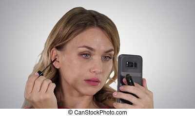 Woman applying black mascara on eyelashes looking in her phone on gradient background.