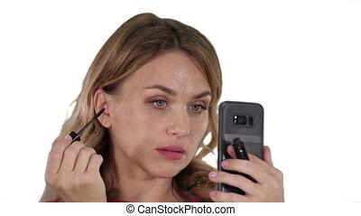 Woman applying black mascara on eyelashes looking in her...