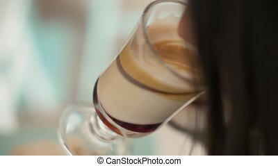 Close up woman drinking coffee latte from glass cup in...