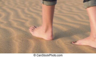 Close up, woman feets walking on golden sand at the beach. -...