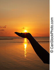 close up woman hand holding sun in hand