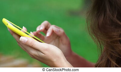 Close up woman hand using smartphone and touching on a blank screen park outdoor
