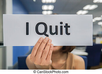 close up woman hand with paper sheet of I quit in workplace