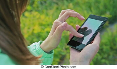 Close-up woman hands using touchscreen phone outdoors