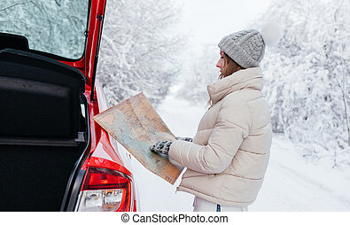 Close-up. Woman holding a map in her hands while searching for a route on the side of the road in winter forest