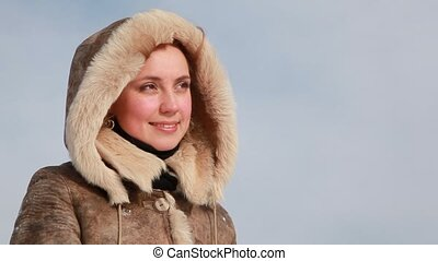 Close Up woman in fur hood, smiling and looks forward