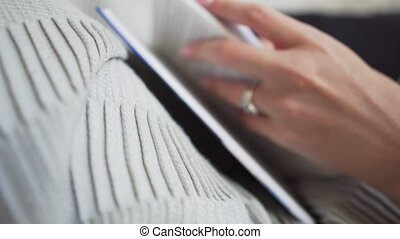 Close-up - woman leafing through pages of a book, holding it on a cozy plaid