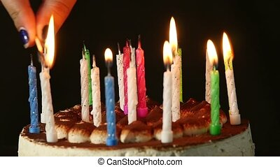 Close-up woman lights candles on tasty birthday cake. Slow...