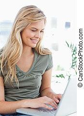 Close up, woman smiling and using her laptop on the couch