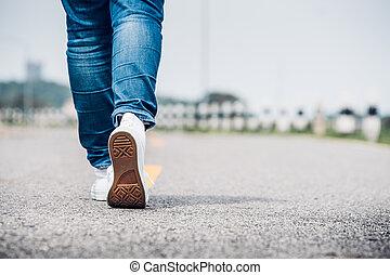 Close up woman wear jean and white sneaker walking forward...