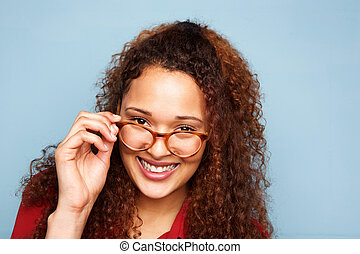 Close up woman with curly hair and glasses smiling against blue background