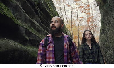 Close up. Woman with long hair and a man with a beard walking along the path of a pedestrian path between the stones during the sunny autumn day