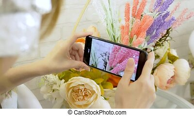 close-up. woman's hands taking mobile photo of flower...
