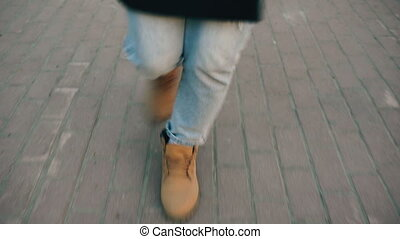 Close up woman's legs dancing on city street