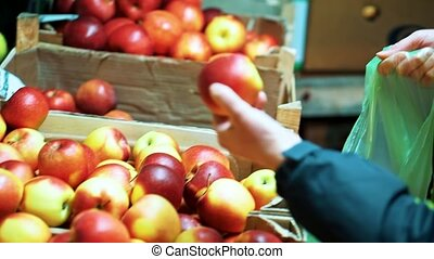 Close up women hands recruit red apples in plastic bag in shop.