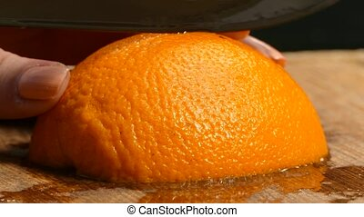 Close-up. Women's hands cut juicy orange wedges