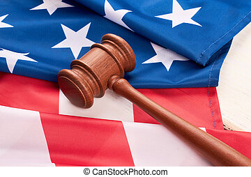 Close up wooden gavel and American flag.