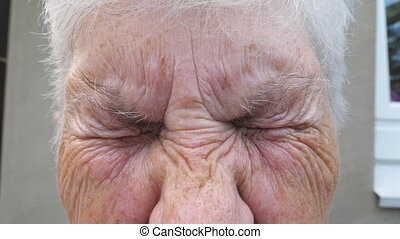 Close up wrinkled face of old grandmother looking into...