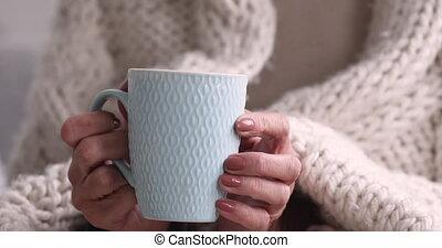 Close up wrinkled female hands holding cup of hot beverage...