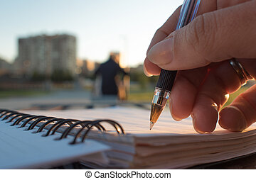 Close-up, writing in a notebook, develop plan of action -...