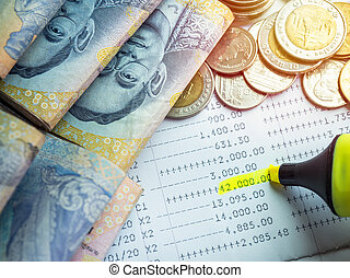 Close-up yellow marker pen highlighting on the deposit money, account statement in saving account passbook.