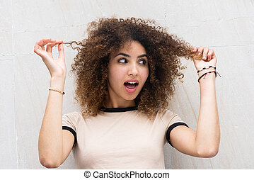 Close up young african american woman holding curly hair with surprised expression on face