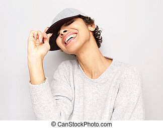 Close up young african american woman laughing with cap by white wall