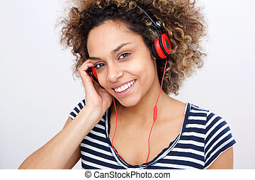 Close up young african american woman listening to music with headphones