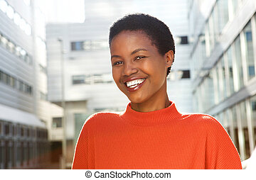 Close up young african american woman smiling outside in city