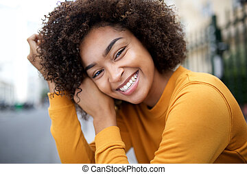 Close up young african american woman smiling with curly hair