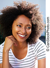 Close up young african woman with curly hair looking away and smiling outdoors