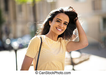 Close up young arabic woman smiling with hand in hair outside