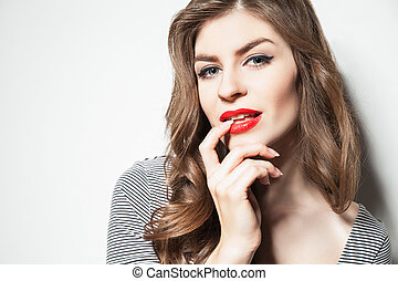 Close-up young brunette in striped body posing against of white wall