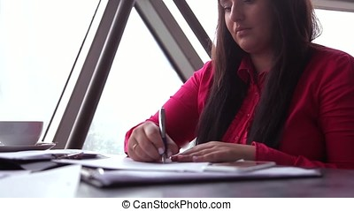 Close-up. Young business woman working with office documents and answering a call