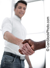close up. young businessman shaking hands with business partner