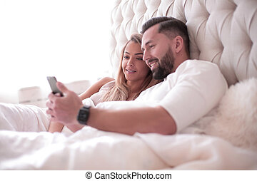 close up. young couple reading e-mails on smartphone