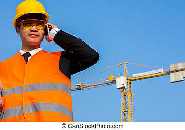 Close up Young engineer in orange shirt stands talking on a mobile phone. Over cranes in the background.