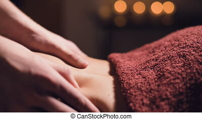 Close-up Young male massage therapist does back massage to a...